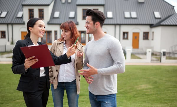 Young Couple With Real Estate Agent Visiting House For Sale In R