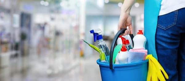 A Cleaning Woman Is Standing Inside A Building Holding A Bucket Fulfilled With Chemicals And Facilities For Tidying.